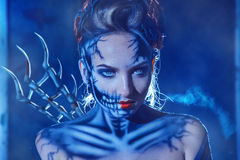 Holoween theme photo of woman with face art of skull on fac. E outdoors stock photo