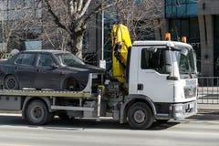 Holownicza ciężarówka z haczykiem i łańcuchem odtransportowywa samochód bez frontowego koła wzdłuż miasto ulicy w ciągu dnia zdjęcie stock