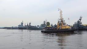 Holownik z militarnymi żeglarzami na tle statki Bałtycka flota Przygotowanie dla marynarka wojenna dnia w Kronstadt
