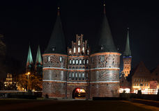 Holstentor and church towers in Luebeck iluminated at night, med Stock Images