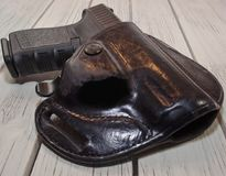 A holstered black pistol on a wooden table. A black 9mm pistol shown in a holster laying on a wooden table Stock Image