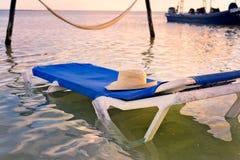 Holu krzesło w oceanie z Kapeluszowy Odpoczywać na wierzchołku Obrazy Stock