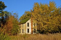 Holuse Abandoned in the Woods. A two story house is abandoned in the autumn woods Stock Photography