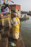 Holy bath in the river Ganges. Woman in a colorful sari on the ghats of Varanasi Stock Photography