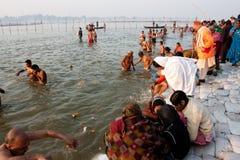 Holy bathing during Kumbha Mela festival. Hindu people bathing in water of sacred Sangam during Kumbh Mela. Tthe largest religious gathering on the planet, in Royalty Free Stock Photography