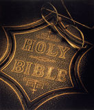 The Holy Bible. An old edition of the Holy Bible with reading glasses on it Stock Image