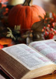 The Holy Bible. A Holy Bible opened to the gospel of John.  The Bible is well used and underlined and is sitting on a table with a centerpiece of pumpkins and Stock Images