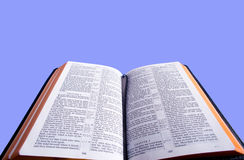 The Holy Bible. An open Bible in front of a blue sky background with copy space.  Bible version is the King James version of the bible which is in the public Royalty Free Stock Image
