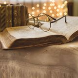 Holy bible book with eyeglasses. Christmas lights on background Stock Photo