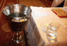Holy Bible and bowl with water prepared for christening ceremony in ortodox church Stock Photo