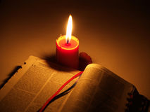Holy Bible and Candle. Holy Bible study and lighted red candle in the dark room Stock Photos