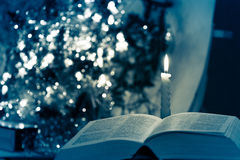 Holy Bible with candle on bokeh Royalty Free Stock Image