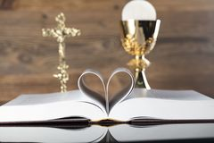 Catholic religion theme - holy communion concept. Holy Bible, the Cross and golden chalice  on wooden background and glass table.  Place for text Royalty Free Stock Photography