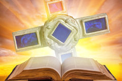 Holy bible and cross. An open bible with blue holy cross against a bright sunny sky filled with light and sunshine Stock Photos
