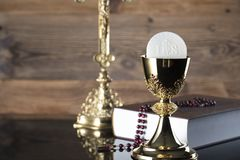 Catholic religion theme - holy communion concept. Holy Bible,the Cross, rosary and golden chalice  on wooden background.  Place for text Royalty Free Stock Photography