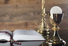 Catholic religion theme - holy communion concept. Holy Bible,the Cross, rosary and golden chalice  on wooden background.  Place for text Royalty Free Stock Photo