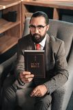 Dark-haired bearded man holding the Holy Bible stock photos