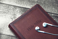 Holy Bible with headphones. Brown Holy Bible with headphones on top Stock Photography
