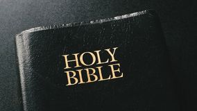 Holy Bible. On black surface. From above view stock video footage