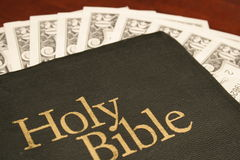 Holy Bible & money. Holy Bible with $20 bills on table for tithing royalty free stock photo