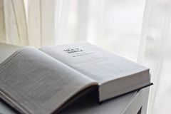 The Holy Bible next to a window Stock Image