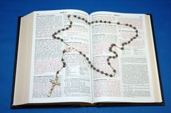 Holy Bible and Rosary. On blue background stock image