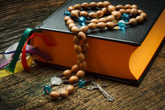 Holy bible. With rosary beads on wooden background Royalty Free Stock Photography