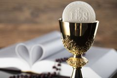 Catholic religion theme - holy communion concept. Holy Bible, rosary and golden chalice  on wooden background and glass table.  Place for text Royalty Free Stock Photo