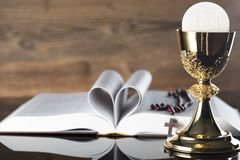Catholic religion theme - holy communion concept. Holy Bible, rosary and golden chalice  on wooden background and glass table.  Place for text Stock Photography