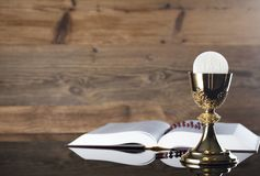 Catholic religion theme - holy communion concept. Holy Bible, rosary and golden chalice  on wooden background.  Place for text Royalty Free Stock Photography