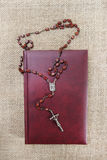 Holy Bible and rosary on jute background Stock Image
