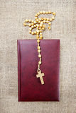 Holy Bible and rosary on jute background Stock Images
