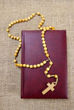 Holy Bible and rosary on jute background Royalty Free Stock Images