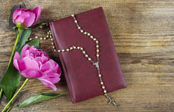 Holy Bible, rosary and lush pink peonies Stock Image