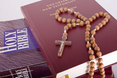 Holy Bible with rosary on pile of old books. Open Holy Bible lying on stack of old books with glasses, cross and beads Royalty Free Stock Photo