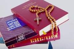 Holy Bible with rosary on pile of old books. Open Holy Bible lying on stack of old books with glasses, cross and beads Royalty Free Stock Images