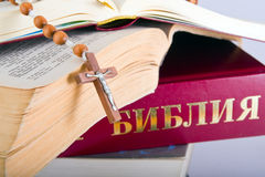 Holy Bible with rosary on pile of old books Royalty Free Stock Image