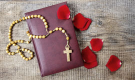 Holy Bible, rosary and red rose petals Royalty Free Stock Photography