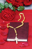 Holy Bible, rosary and stunning red roses Royalty Free Stock Photos