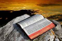 Holy Bible and skies. Open old bible on a rock on a beautiful sky at sunset background Stock Image