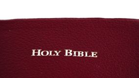 Holy Bible slowly moving over white background stock footage