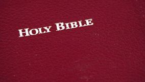 Holy Bible slowly moving over white background stock video