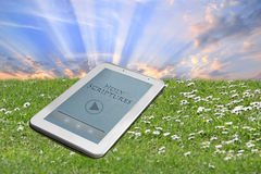 Holy bible tablet. Photo of holy bible downloaded onto a tablet device against green grass and sky sun rays background Stock Photography