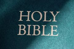 Holy Bible title closeup in sunlight. Religion and faith concept. Religious literature. Bible . Christianity background. Vintage Bible book in light stock image