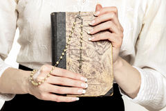 Holy Bible and white rosary in beautiful hands Stock Photo