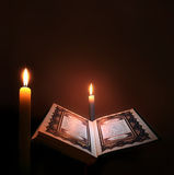 Holy book of Islam with candle light. Stock Photos