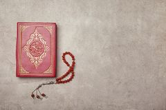 Holy book of Muslims and prayer beads. On gray background Royalty Free Stock Images