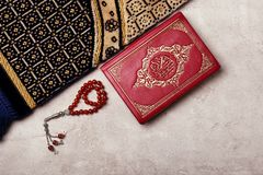 Holy book of Muslims, prayer beads and rug. On gray background Stock Photography