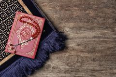 Holy book of Muslims, prayer beads and rug. On wooden background Royalty Free Stock Photo