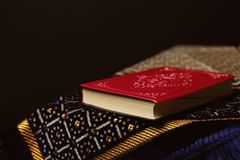Holy book of Muslims and prayer rug. Against black background Stock Photos